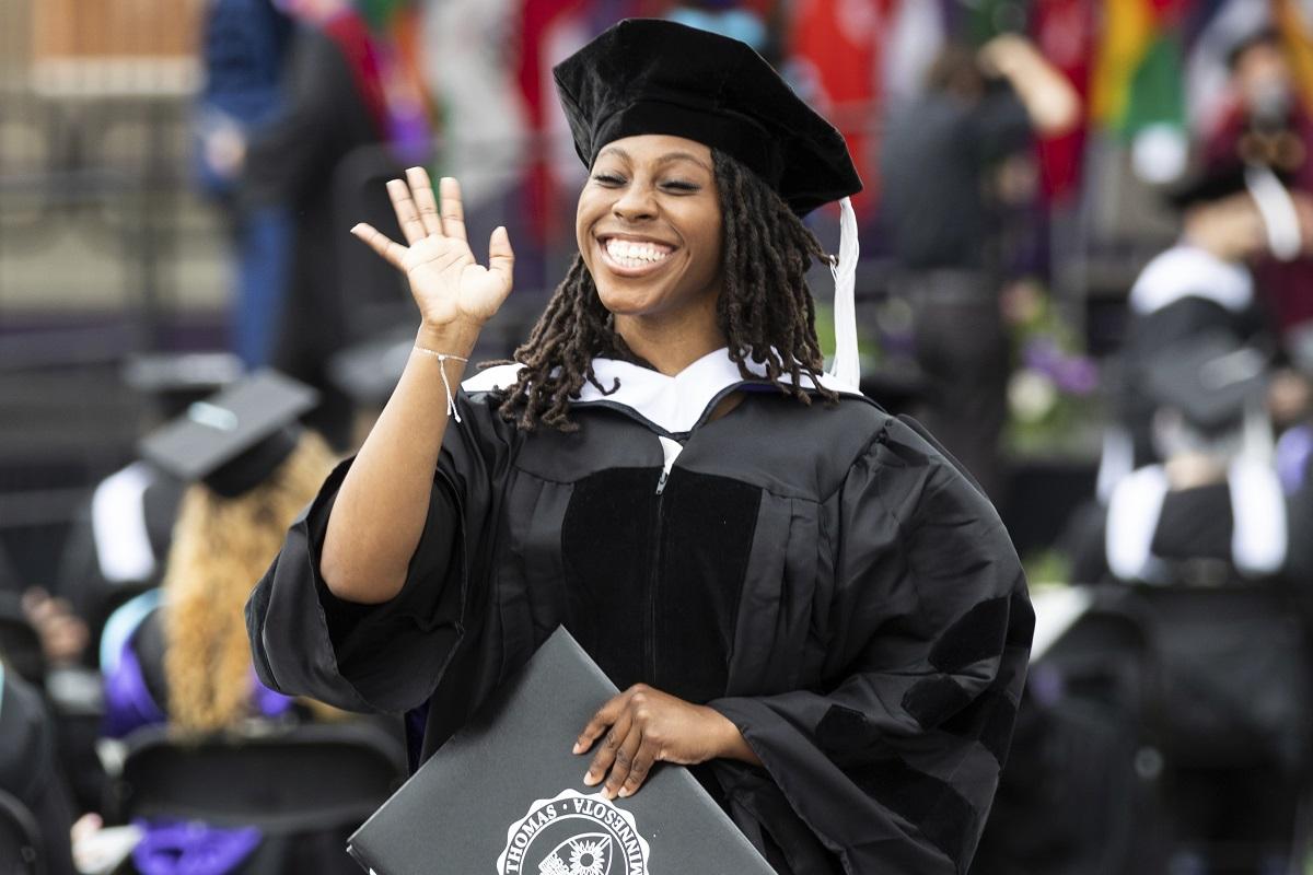 Student waiving at graduation